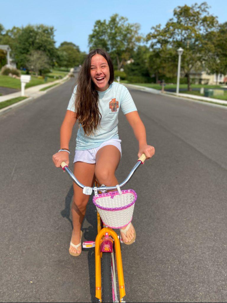 Young Girl Riding Bike wearing DexterDogUSA shirt