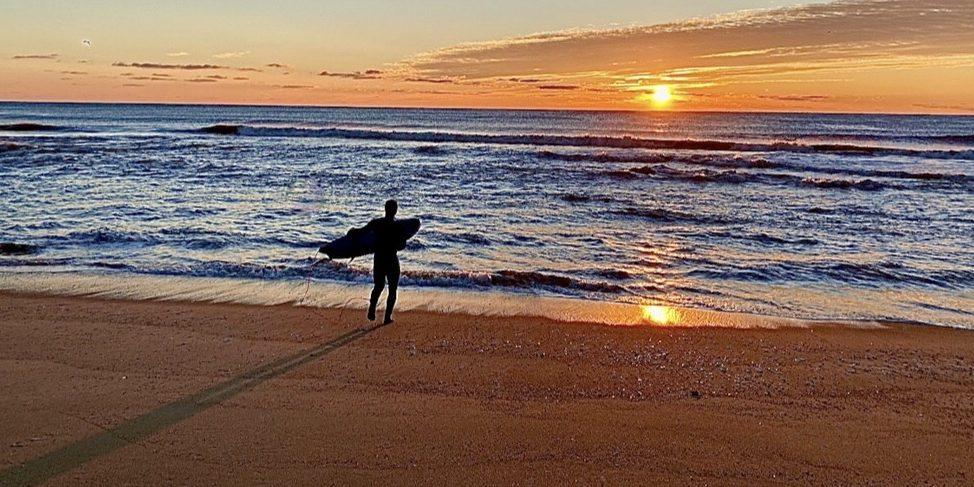 Surfer at sunset on beach